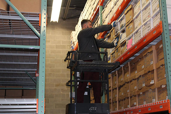 Employee in warehouse pulling boxes